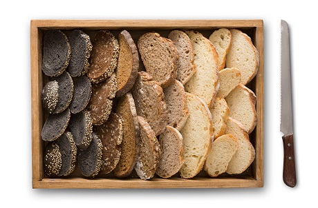 Sliced sorts of bread gradient background isolated at white. Black, rye and white loaves in wooden frame with knife. Food art, bakery and grocery concept.